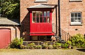 image of rabbit hutch  - Horizontal shot of old courtyard with redbrick house and iron steps leading to a red porch - JPG
