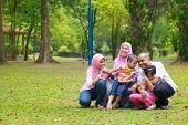 picture of southeast asian  - Happy family having fun at outdoor green lawn - JPG