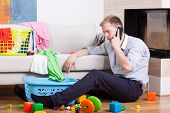 stock photo of babysitting  - Image of man alone at home on the phone with child - JPG