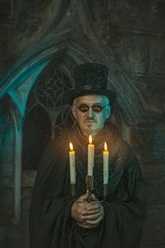 stock photo of sorcerer  - Evil sorcerer with the chandelier in the hands of the night - JPG