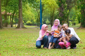 stock photo of southeast  - Happy family having fun at outdoor green lawn - JPG