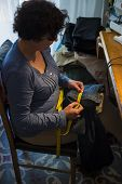 stock photo of sewing  - Middle aged woman sewing in a sewing workshop - JPG