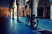 stock photo of arcade  - Cyclists at the column in the arcade in the early morning in Mantova. Italy
