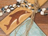 stock photo of mother-of-pearl  - marine theme in interior design with wooden flooring with inlaid dolphin aged ceramic tiles mother of pearl beads salted wood and rough twine - JPG