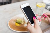 foto of internet-cafe  - Woman holding new generation mobile phone in cafe - JPG
