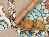 stock photo of mother-of-pearl  - selection of materials for interior decoration in a nautical style with ceramic mosaics similar to the sea pebbles a linen cloth pearl beads salted tree and plant seeds - JPG