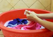 image of tub  - Two hands washing clothes in red tub - JPG