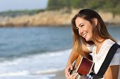 stock photo of guitar  - Beautiful guitarist woman playing guitar on the beach with the sea in the background - JPG