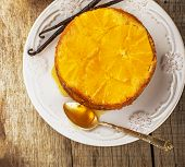 stock photo of testis  - Home made whole testy orange cake with honey glaze and natural vanilla on wooden background - JPG