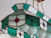 stock photo of light fixture  - Stained glass light fixture hanging in a home - JPG