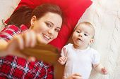 pic of selfie  - Cute little baby girl and her mother taking selfie on a blanket in a living room - JPG