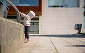 stock photo of hoodie  - Little girl with sneakers and hoodie training hard with a metal railing in a city square