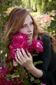 stock photo of auburn  - Beautiful young woman with auburn hair and green eyes admiring roses in the rosary
