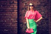 image of toned  - Beautiful Fashionable Woman Standing at the Old Brick Wall Background - JPG