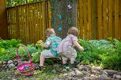 pic of easter basket eggs  - A basket full of colorful eggs sits beside two boys finding eggs during an Easter egg hunt outside in a beautiful garden in the spring - JPG