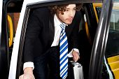 stock photo of cabs  - Young businessman getting out of a taxi cab - JPG
