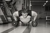 foto of lifting-off  - Man doing workout with heavy dumbbell - JPG