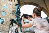 stock photo of perseus  - Young woman taking photo of statue perseus with the head of medusa in florence italy - JPG