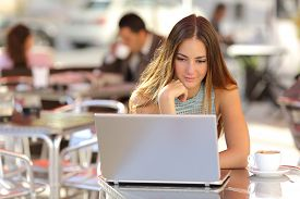 picture of self-employment  - Attentive woman watching media in a laptop in a coffee shop with people in the background - JPG