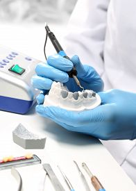 stock photo of false teeth  - Prosthetics hands while working on the denture - JPG