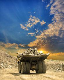 stock photo of iron ore  - Heavy dump truck carrying the iron ore on the opencast mining on sunset - JPG