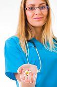 stock photo of prescription  - Kind attractive doctor offering prescription drugs and nutricion supplements - JPG