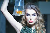 foto of goldfish  - Striking young girl with bright makeup and blonde curly hair holding cellophane package aquarium with goldfish horizontal photo - JPG