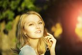 image of natural blonde  - Portrait of smiling lively pretty young woman with blonde hair standing outdoor in sunset on natural background horizontal picture - JPG