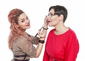 pic of makeup artist  - Professional makeup artist making makeup to a model isolated on white background - JPG