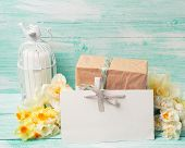 foto of text-box  - Narcissus flowers empty tag for text candle box with present on turquoise painted wooden planks - JPG