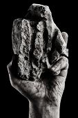 stock photo of gallows  - Rock in male dirt hand on black background - JPG