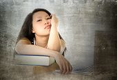 stock photo of boring  - young pretty chinese asian student woman with computer bored tired and overworked leaning on school books studying for exam in education concept - JPG
