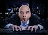 picture of addict  - young businessman late at night in office typing on computer keyboard with funny face expression on watching porn online and internet chat and social network addiction concept - JPG