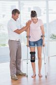 image of crutch  - Doctor helping his patient walking with crutch in medical office - JPG