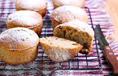 stock photo of icing  - Whole meal muffins with raisin coated with icing on wire rack - JPG