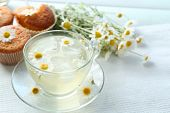 image of chamomile  - Cup of chamomile tea with chamomile flowers and tasty muffins on color wooden background - JPG