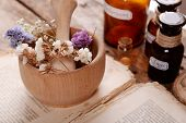 picture of roughage  - Old book with dry flowers in mortar and bottles on table close up - JPG