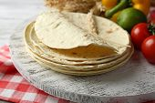 stock photo of whole-wheat  - Stack of homemade whole wheat flour tortilla and vegetables on cutting board - JPG