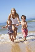 stock photo of chase  - Mother Chasing Children Along Beach - JPG
