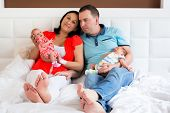 stock photo of twin baby girls  - Happy parents cuddling boy and girls twins - JPG