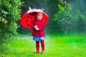 stock photo of rainy weather  - Little girl with red umbrella playing in the rain - JPG