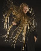 picture of hair blowing  - Smiling Blond Woman Wearing Black Dress Standing in Studio with Black Background with Long Hair Blowing in Strong Wind - JPG