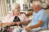 image of visitation  - Adult Son Visiting Senior Mother Sitting On Sofa At Home Doing Crochet - JPG