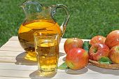 pic of pitcher  - Apple juice in a glasswith a pitcher and apples on a wood table - JPG