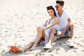 foto of couple sitting beach  - Young couple sitting on a sandy beach - JPG