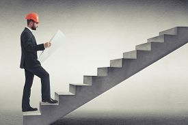 pic of follow-up  - businessman in orange hardhat holding blueprint and following up on concrete stairs in grey empty room - JPG