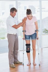 stock photo of crutch  - Doctor helping his patient walking with crutch in medical office - JPG