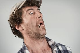 stock photo of shock awe  - Shocked redneck jumps back in fear as he smokes his cigarette - JPG