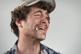 image of sarcastic  - Sarcastic redneck laughs hysterically while smoking a cigarette - JPG
