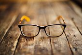 Glasses  Lie On The Dark Wooden Table.   Black Orange  Glasses poster